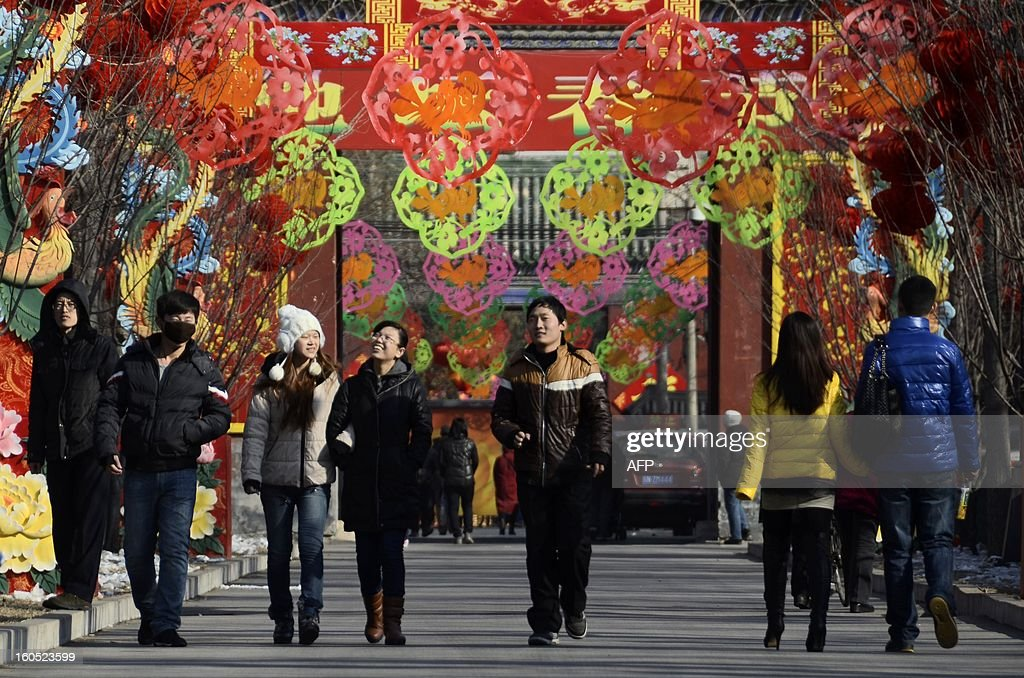 People walk along a road decorated by colorful decals for the upcoming Lunar New Year, at a park in Beijing on February 2 , 2013. The Chinese New Year know locally as the Spring Festival, causes the world's largest annual migration of people with millions of travellers boarding public transport to journey across the vast country for the Lunar New Year celebrations. The government estimates the number of passenger trips on trains, planes, boats and buses will reach 3.2 billion during the holiday, up 9.1 percent from last year.