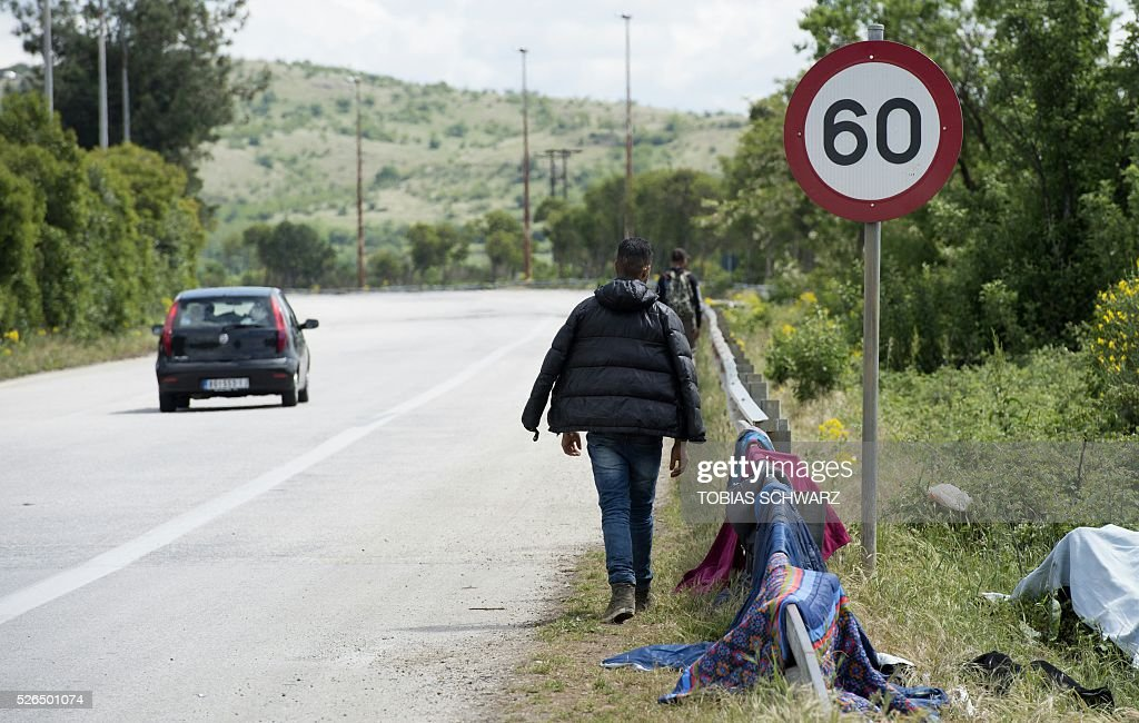 People walk along a road next to a makeshift camp for migrants and refugees near the village of Idomeni not far from the Greek-Macedonian border on April 30, 2016 Some 54,000 people, many of them fleeing the war in Syria, have been stranded on Greek territory since the closure of the migrant route through the Balkans in February. / AFP / TOBIAS
