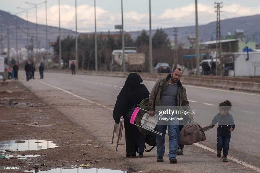 People walk along a road to a temporary housing complex located at the closed Turkish border gate on February 7, 2016 in Kilis, Turkey. According to Turkish officials some 35,000 Syrian refugees have massed on the Syrian/Turkish border after fleeing Russian airstrikes and a regime offensive surrounding the city of Aleppo in northern Syria.