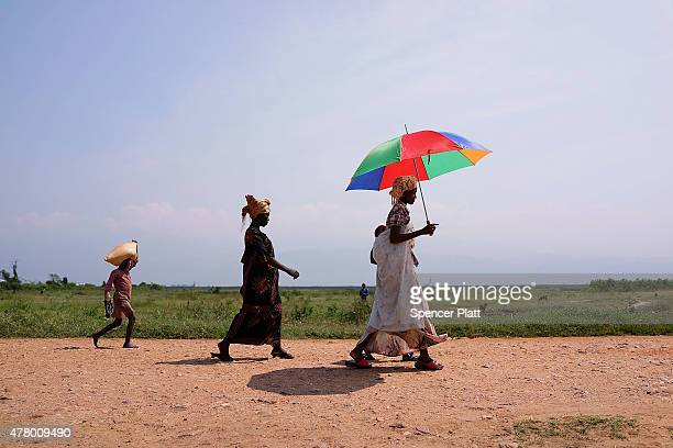 People walk along a rural path outside of the capital Bujumbura on June 21 2015 in Bujumbura Burundi The head of Burundi's influential rights group...