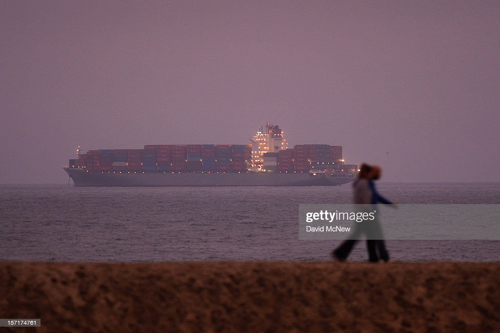 People walk along a sand berm with a view of anchored container ships which cannot enter the ports of Los Angeles and Long Beach to load and unload cargo because of a strike by the International Longshore and Warehouse Union Local on November 29, 2012 in Seal Beach, California. The strike is the largest work stoppage at the ports of Los Angeles and Long Beach since a lockout by shipping companies in 2002, which prompted President George W. Bush to intervene with a court injunction to resolve the standoff.