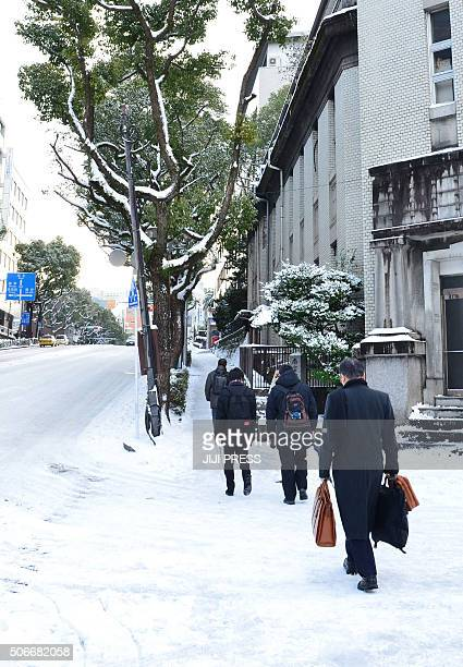 People walk along a slippery snowcovered road in Nagasaki on Japan's southern island of Kyushu on January 25 2016 Five people died and more than 100...