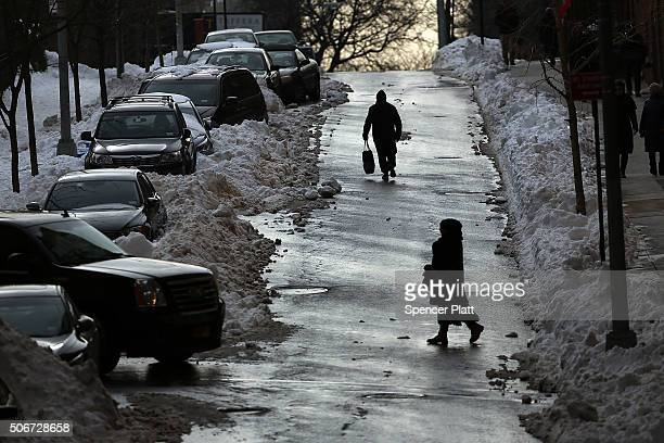 People walk along a slush covered street on the first workday following a blizzard that set a new singleday record for snowfall in both New York and...