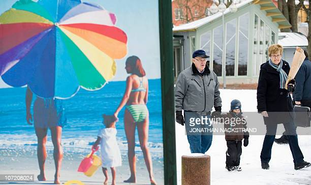 People walk along a snow covered street past an advertisement featuring a pictures of a beach scene in Mariehamn on November 18 2010 AFP...