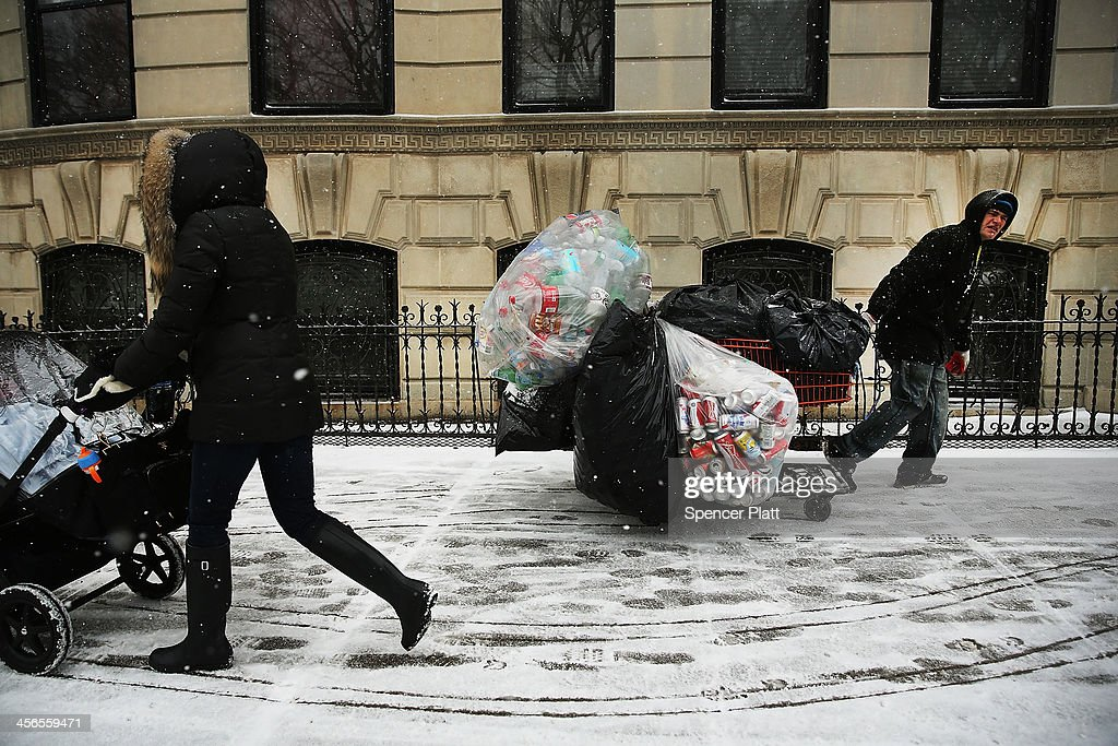People walk along a snowy street during a snow storm on December 14, 2013 in the Brooklyn borough of New York City. Much of the Northeast was hit by a storm stretching over 1,000 miles that could result in at least a foot of snow on parts of New England.