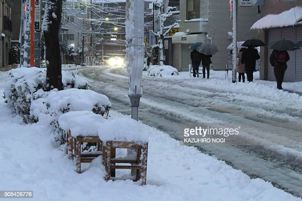 People walk along a street covered with snow as they head to a subway station in Tokyo on January 18 2016 Tokyo had its first snow of the season amid...
