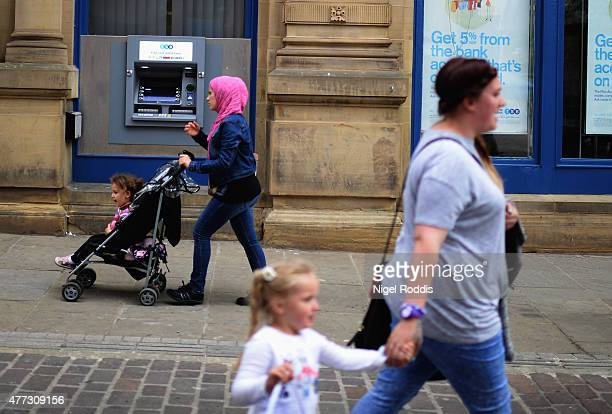 People walk along a street in Bradford on June 16 2015 in Bradford England Three sisters from Bradford are feared to have travelled to Syria with...