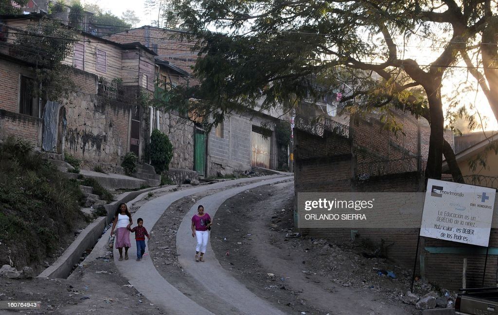 People walk along a street in the poor community of Campo Cielo, in Tegucigalpa on February 5, 2013. Honduras' notorious street gangs, especially the Mara 18 and the Mara 13 or Salvatrucha, have imposed a curfew and are charging a 'war tax' in some of the capital's poorest sectors -- thing which led the police to deploy more personnel in theses areas. The violent maras are active in murders, extorsion, drug dealing, arms trafficking and other crimes. The United Nations says Honduras, a country plagued by powerful street gangs and drug-related violence, has the world's highest homicide rate. In 2010 it was 82 per 100,000 inhabitants, and rose to 86 in 2011. By comparison, in drug-cartel-plagued Mexico, for instance, the rate was about 18 in 2010. AFP PHOTO/Orlando SIERRA