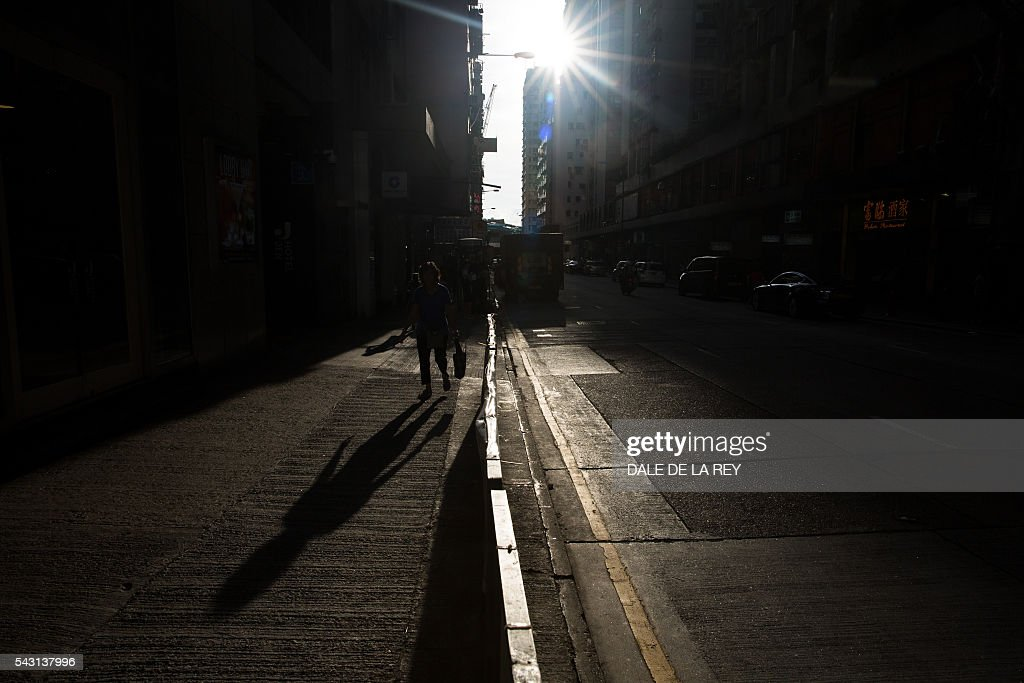 People walk along a street on a hot day in Hong Kong on June 26, 2016. The official Hong Kong Observatory issued a hot weather warning on June 26 as a subtropical ridge continued to bring very hot weather to southern China. / AFP / DALE