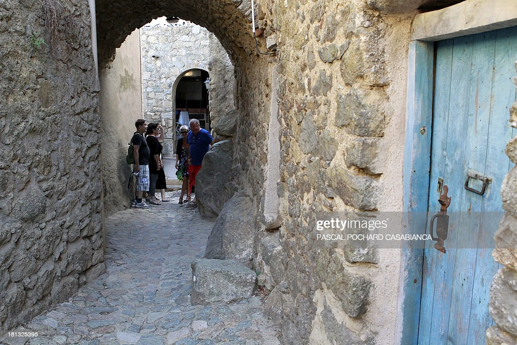 People walk along an alley on September 19, 2013 in San Antonino village, on the French Mediterranean island of Corsica. San Antonino is listed as one of the most beautiful villages of France. AFP PHOTO / PASCAL POCHARD-CASABIANCA
