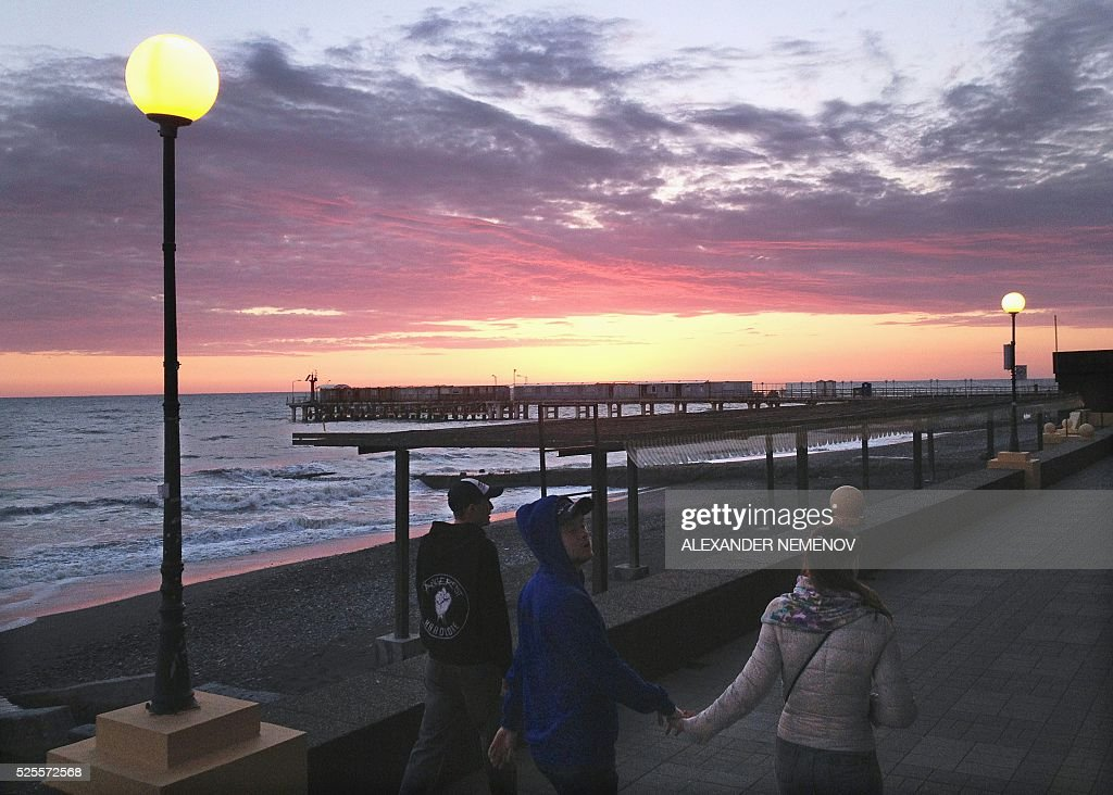 People walk along an embankment in Sochi on April 28, 2016, a day ahead of the Formula One Grand Prix at the Sochi Autodrom circuit. / AFP / ALEXANDER