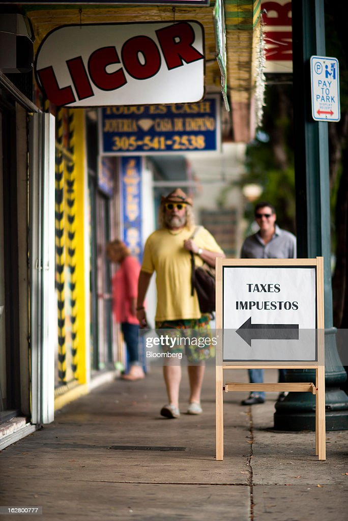People walk along Calle 8 or, Eighth street, in the Little Havana district of Miami, Florida, U.S., on Wednesday, Feb. 20, 2013. U.S. exports in the travel and tourism sector reached $168.1 billion in 2012, up 10.1 percent from the year-ago level of $152.7 billion, according to data released Feb. 22 by the Commerce Department's International Trade Administration. Photographer: Ty Wright/Bloomberg via Getty Images