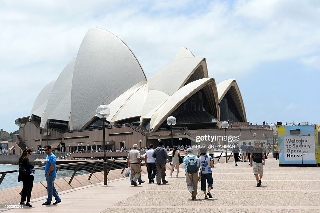 People walk along Circular Quay towards Sydney's Opera House on November 13, 2012.