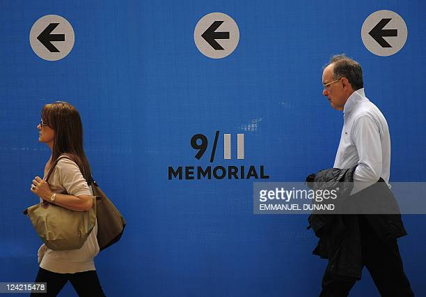 People walk along construction fences surrounding the 9/11 Memorial site in New York September 8 2011 New York is getting ready to commemorate the...