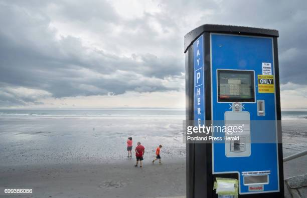 People walk along Long Sands Beach in York on Monday June 20 2017 behind a parking meter with the slot for cash payments taped over New parking...