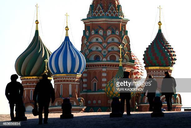 People walk along Moscow's Red Square with St Basil's Cathedral in the background on February 17 2015 AFP PHOTO / YURI KADOBNOV