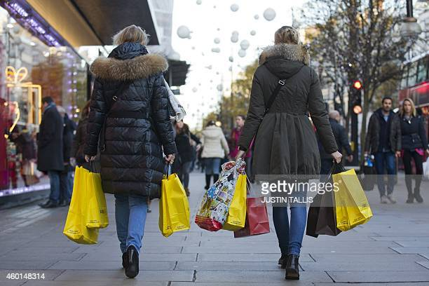 People walk along Oxford Street with carrier bags full of shopping in central London on December 8 2014 AFP PHOTO/JUSTIN TALLIS