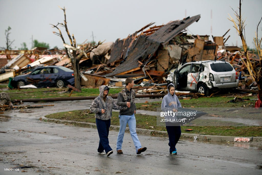 People walk along Robinson Avenue near a destroyed home on May 21, 2013 in Moore, Oklahoma. Families returned to a blasted moonscape that had been an American suburb Tuesday after a monstrous tornado tore through the outskirts of Oklahoma City, killing at least 24 people. Nine children were among the dead and entire neighborhoods vanished, with often the foundations being the only thing left of what used to be houses and cars tossed like toys and heaped in big piles. AFP PHOTO/Joshua LOTT