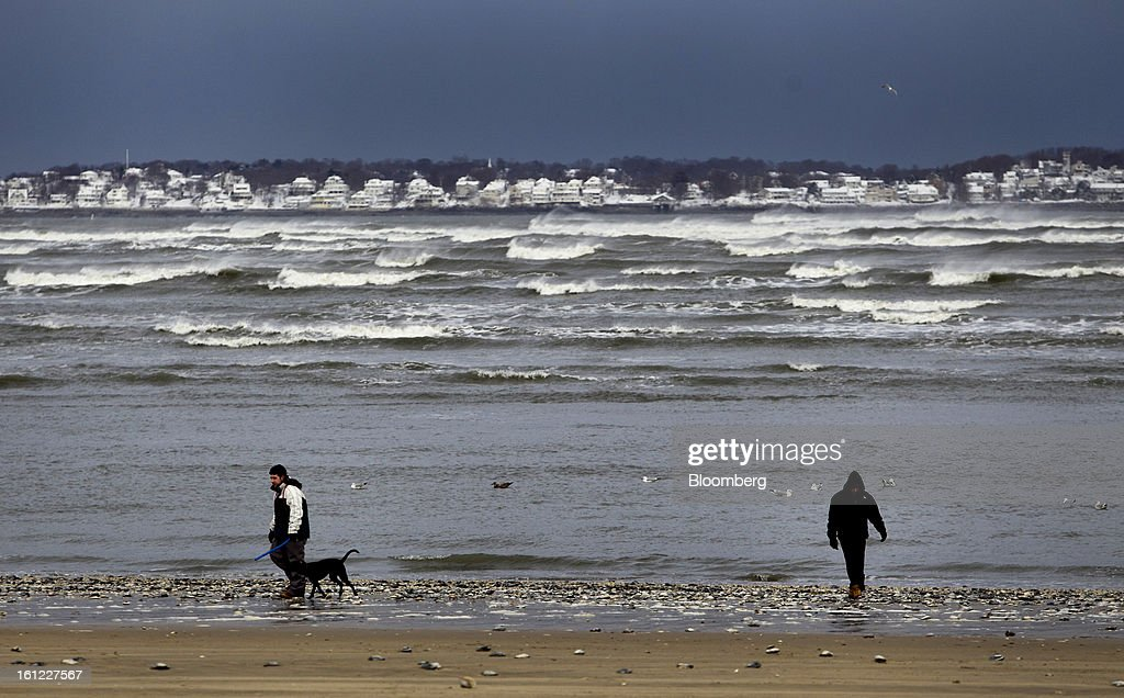 People walk along the beach after Winter Storm Nemo in Revere, Massachusetts, U.S., on Saturday, Feb. 9, 2013. More than two feet of snow fell on parts of the U.S. Northeast as high winds left hundreds of thousands of people in the region without power, closed highways and forced the cancellation of 4,700 flights. Photographer: Kelvin Ma/Bloomberg via Getty Images