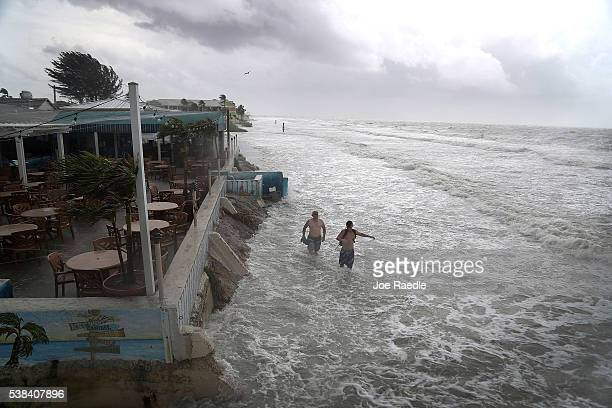 People walk along the beach as waves from Tropical Storm Colin crash along the shore on Fort Myers Beach on June 6 2016 in Fort Myers Florida The...