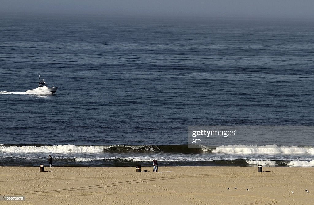 People walk along the beach at Santa Monica California on March 11 as tsunami warnings were issues along the US west following the 89magnitud...