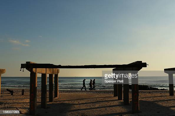 People walk along the beach next to the remains of the boardwalk in the Rockaway on December 13 2012 in New York City Much of the Rockaway...