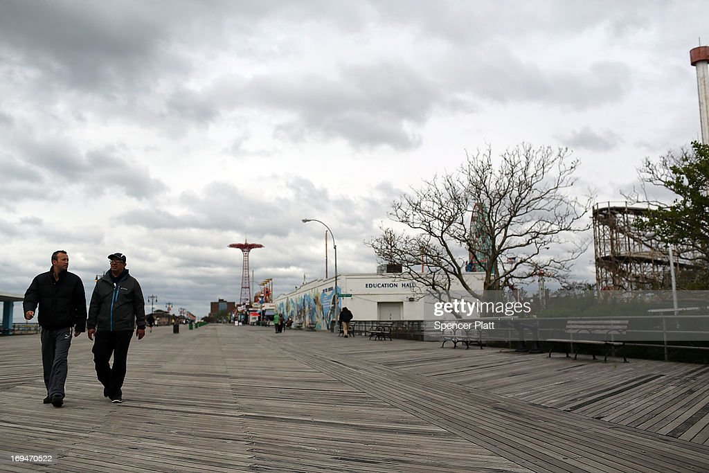 People walk along the boardwalk at the beach at Coney Island on the first weekend of city beaches re-opening to the public on May 25, 2013 in the Brooklyn borough of New York City. While warmer weather and sunny skies are expected for the remainder of the holiday weekend, cool temperatures and rain kept area beaches largely empty.