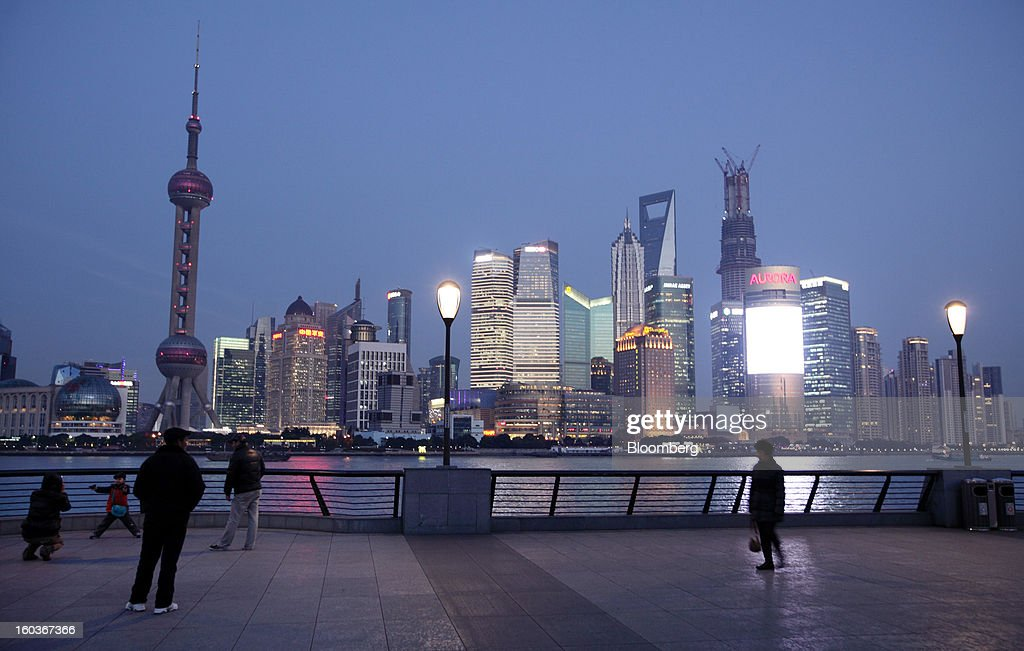 People walk along the bund as commercial buildings stand in the Pudong area at night in Shanghai, China, on Monday, Jan. 28, 2013. China's economic growth accelerated for the first time in two years as government efforts to revive demand drove a rebound in industrial output, retail sales and the housing market. Photographer: Tomohiro Ohsumi/Bloomberg via Getty Images