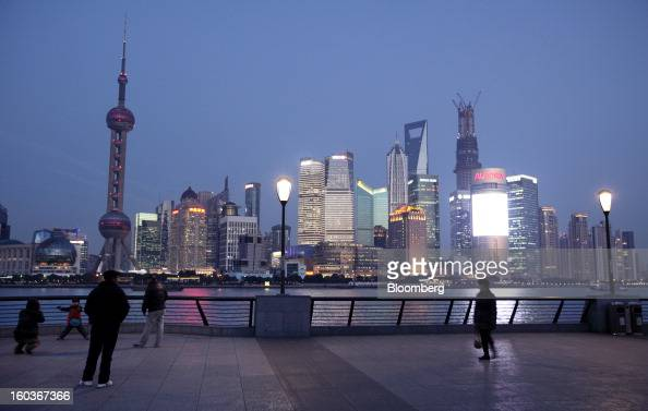 People walk along the bund as commercial buildings stand in the Pudong area at night in Shanghai China on Monday Jan 28 2013 China's economic growth...