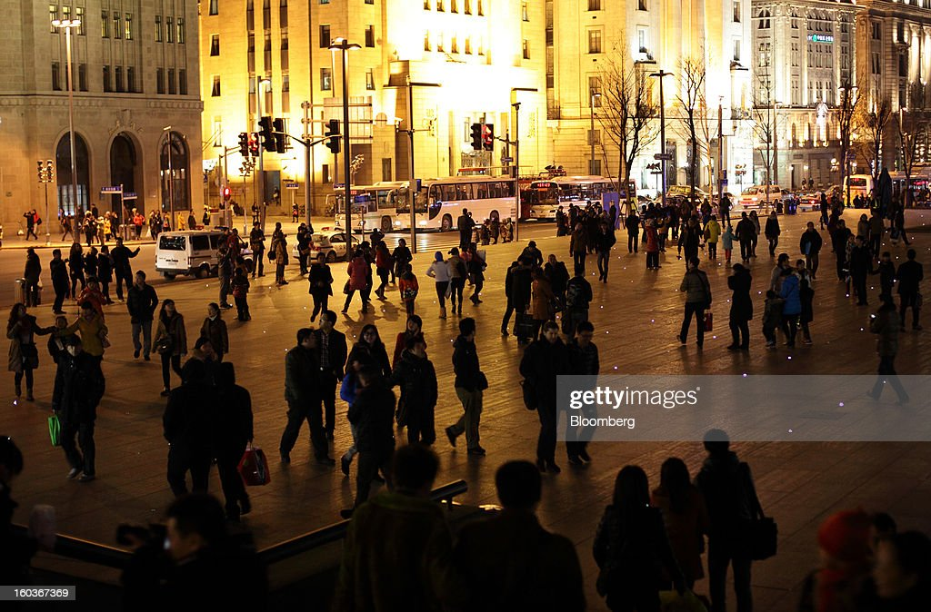 People walk along the Bund at night in Shanghai, China, on Monday, Jan. 28, 2013. China's economic growth accelerated for the first time in two years as government efforts to revive demand drove a rebound in industrial output, retail sales and the housing market. Photographer: Tomohiro Ohsumi/Bloomberg via Getty Images