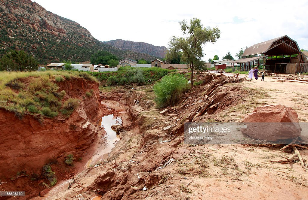People walk along the edge of a gully at the spot where two vans were swept away the day before into Short Creek on September 15 2015 in Hildale Utah...