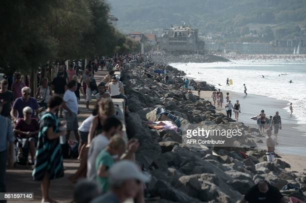People walk along the Grande Plage beach in Hendaye southwestern France on October 15 2017 as unusually warm autumnal temperatures reach 30 degree...
