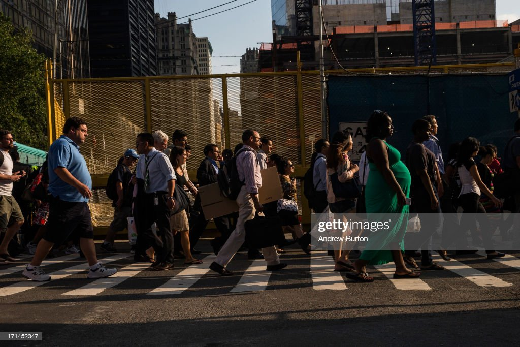 People walk along the northern edge of the Ground Zero construction zone on June 24, 2013 in New York City. Construction began on One World Trade Center, the primary building of the new site, on April 27, 2006 and the final piece of the tower was installed on May 10, 2013, making it the tallest building in the Western Hemisphere. Construction is still ongoing on the surrounding complex.