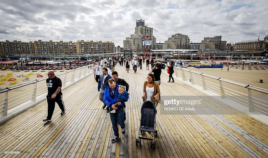 People walk along the renovated upper deck of the pier at the beach of the Dutch resort town of Scheveningen near the Hague on July 18 2015 The...