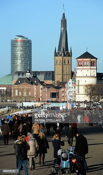 People walk along the Rhine River promenade on February 2 2014 in Duesseldorf western Germany AFP PHOTO / PATRIK STOLLARZ