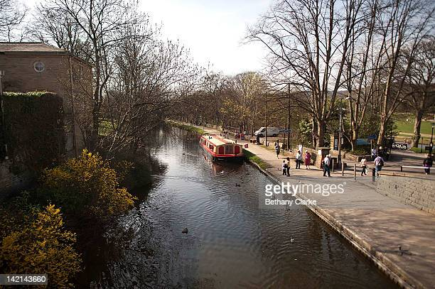 People walk along the River Aire at Saltaire Village World Heritage Site on March 30 2012 in Bradford United Kingdom Saltaire is named after Sir...