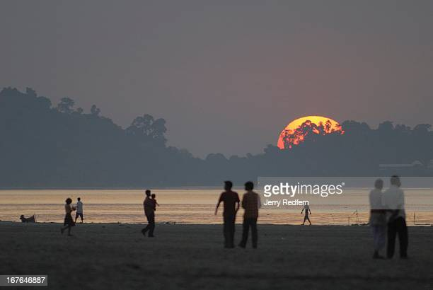 People walk along the smelly muddy sewagestrewn banks of the Brahamaputra River as it passes Guwahati during the dry season Untreated waste from the...