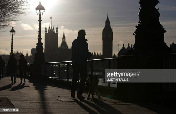 People walk along the South Bank next to the River Thames with the Houses of Parliament in the background during a spell of winter sunshine in London...