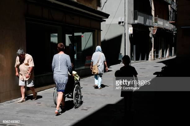 People walk along the the main street of Ripoll on August 21 2017 Spanish police said on August 21 2017 that they have identified the driver of the...