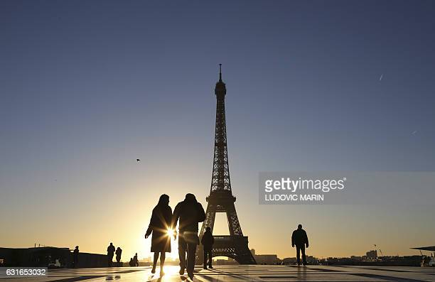 People walk along the Trocadero Plaza as the sunrises behind the Eiffel Tower on a cold Paris morning on January 14 2017 / AFP / LUDOVIC MARIN