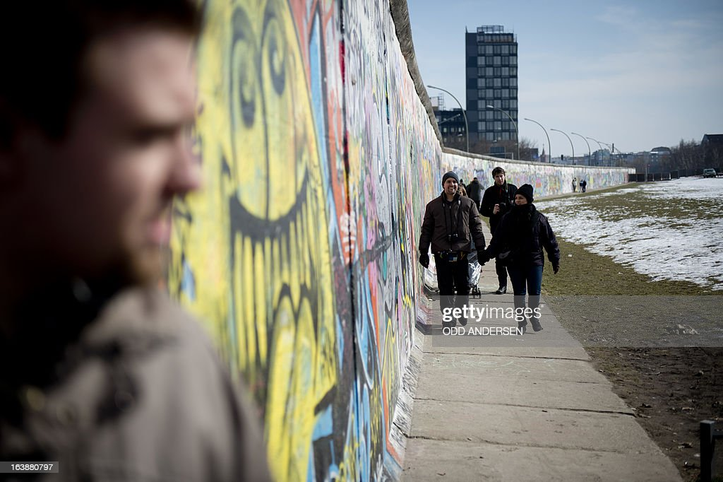 People walk along the Wall prior to US actor and singer David Hasselhoff (unseen) touring the East Side Gallery part of the remains of the former Wall in Berlin on March 17, 2013. The former Bay Watch star came to the German capital to lend his support to the movement for that want to preserve the 1,3km long stretch of the cold war symbol and keep the land along river Spree as public land.