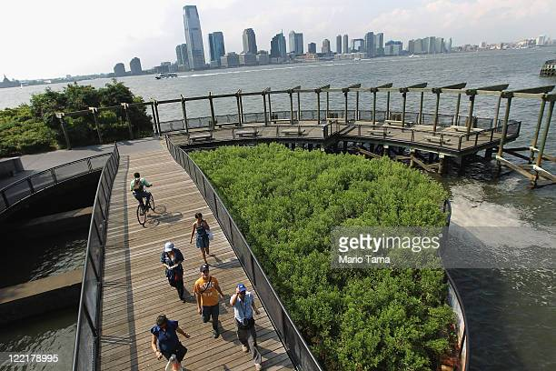 People walk along the waterfront in Battery Park City before the arrival of Hurricane Irene on August 26 2011 in New York City New York City Mayor...