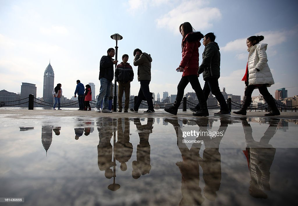 People walk along the waterfront in the Pudong area of Shanghai, China, on Saturday, Feb. 9, 2013. China's services industries grew at the fastest pace since August as gains in retailing and construction aid government efforts to drive a recovery in the world's second-biggest economy. Photographer: Tomohiro Ohsumi/Bloomberg via Getty Images