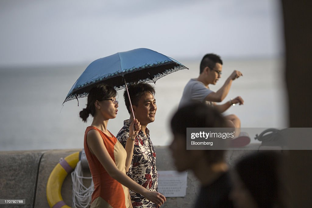 People walk along the waterfront in the Stanley area of Hong Kong, China, on Sunday, June 16, 2013. A shortage of housing, low mortgage costs and a buying spree by mainland Chinese have led home prices to more than double since the beginning of 2009, shrugging off repeated attempts by the government to curb gains amid an outcry over affordability. Photographer: Jerome Favre/Bloomberg via Getty Images