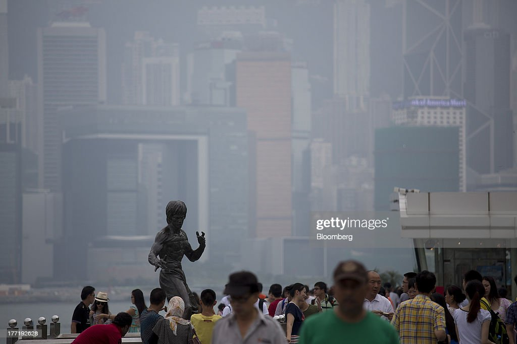 People walk along the waterfront in the Tsim Sha Tsui area of Hong Kong, China, on Thursday, Aug. 22, 2013. Hong Kongs air pollution index reached very high level today as a tropical storm that passed through Taiwan trapped pollutants and blanketed the city in haze, triggering a government health warning. Photographer: Jerome Favre/Bloomberg via Getty Images
