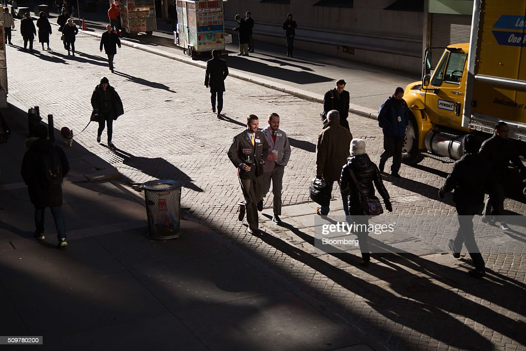 People walk along Wall Street before the opening bell of the New York Stock Exchange (NYSE) in New York, U.S., on Friday, Feb. 12, 2016. U.S. stocks halted a five-day slide that dragged global equities into a bear market, as oil rebounded from a 12-year low and bank shares surged. Photographer: Michael Nagle/Bloomberg via Getty Images
