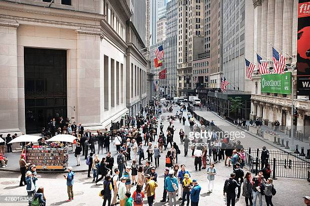 People walk along Wall Street in lower Manhattan on June 5 2015 in New York City New numbers which were released by the government today showed that...