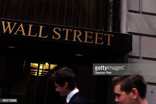 People walk along Wall Street in the financial district on July 9 2015 in New York City The International Monetary Fund announced on Thursday that...