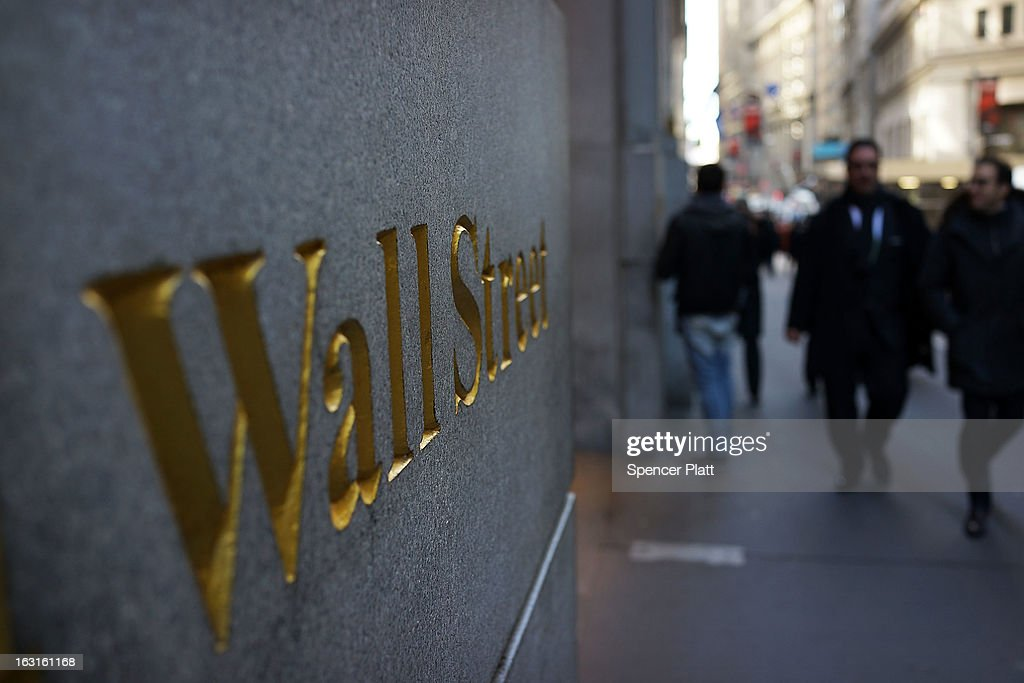People walk along Wall Street near the New York Stock Exchange on March 5, 2013 in New York City. The Dow Jones industrial average rallied to a record high on Tuesday to close for the day at 14,253.77, beating its old 2007 record.