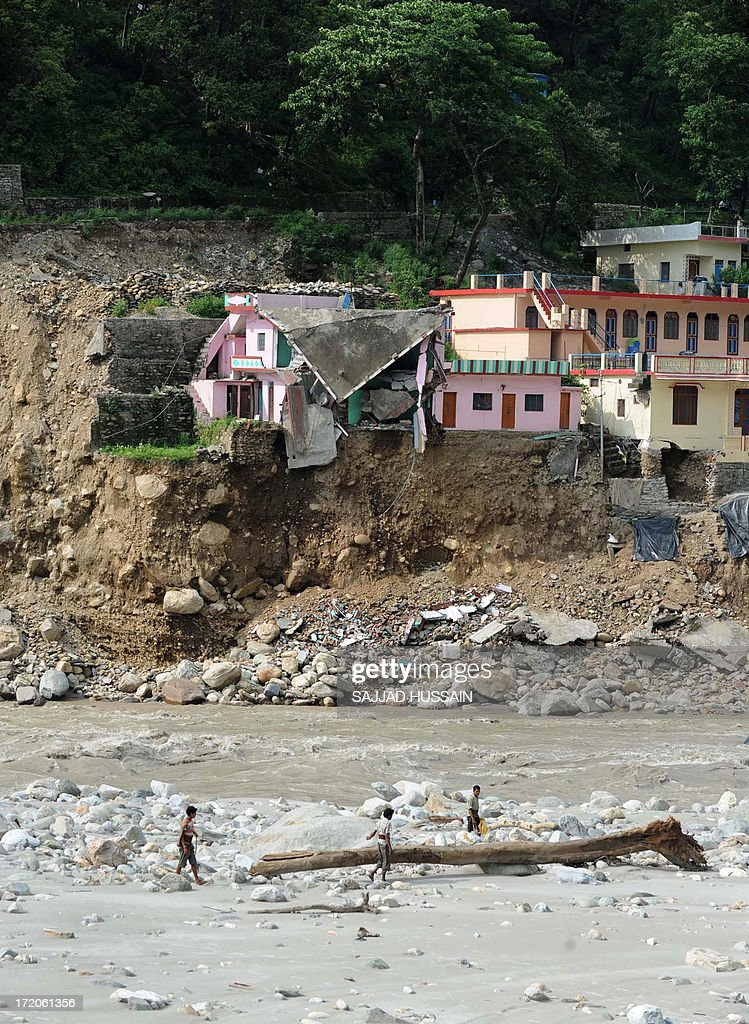 People walk alongside the Mandakini river near a damaged house at Silli, in the flood affected area of northern Uttarakhand state on July 1, 2013. Construction along river banks will be banned in a devastated north Indian state amid concerns unchecked development fuelled last month's flash floods and landslides that killed thousands, the state's top official said July 1. AFP PHOTO/ SAJJAD HUSSAIN